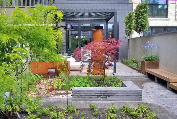 moderne patiotuin met waterelement en weelderig groen