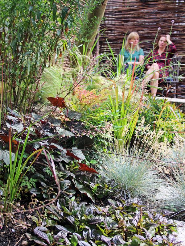 tuin met gekleurde bladplanten en gevlochten schutting wilgentenen