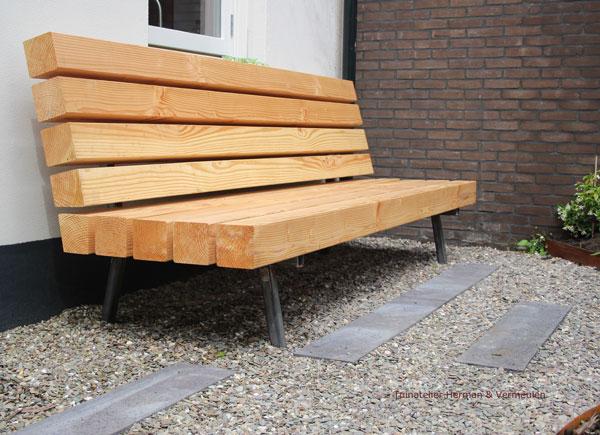 een zitbankje gemaakt van houten balken in de tuin