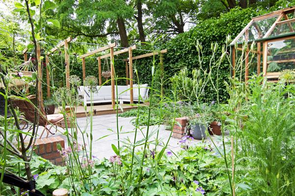 een groene weelderige tuin met gemetselde zitmuurtjes en een moi houten kasje
