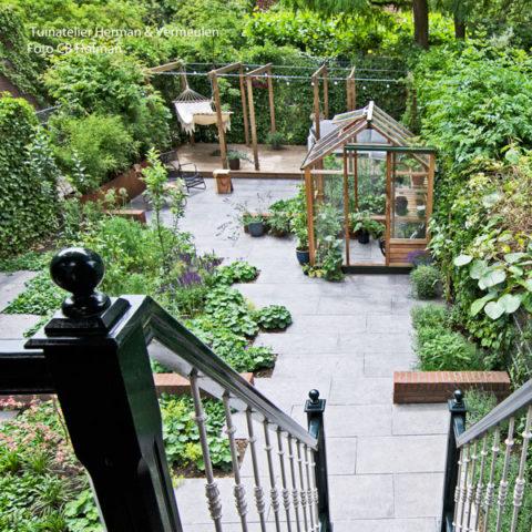 groene en moderne stadstuin met mooi houten tuinkasje