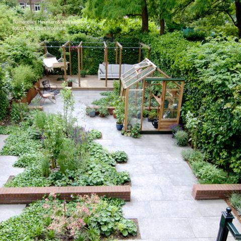 moderne groene tuin met verspringende tegels en een houten kas en pergola