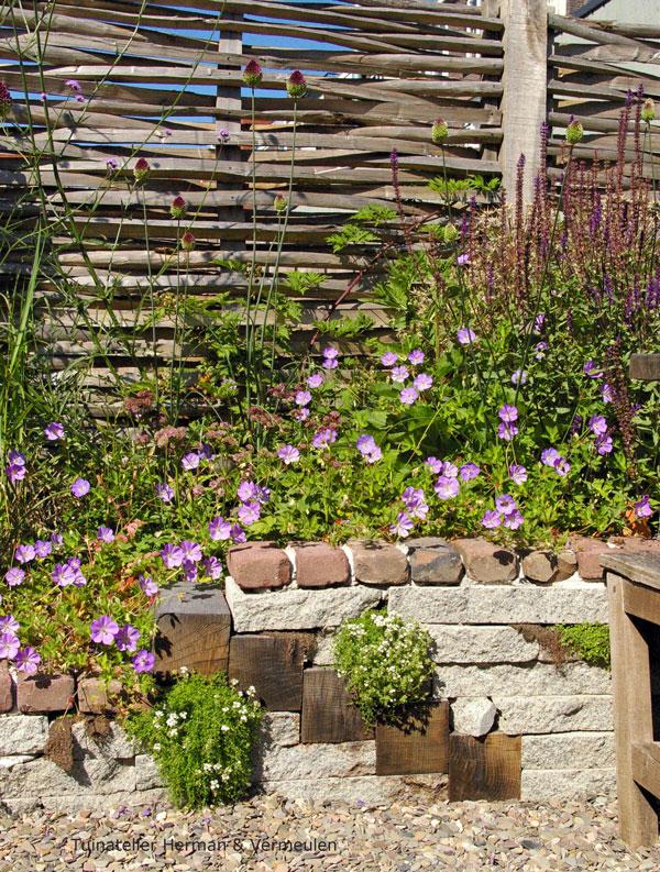 natuurlijke tuin met gevlochten schutting en natuurlijk stapelmuurtje