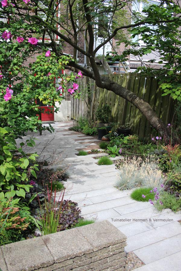 tuin met zitmuurtjes en verspringend pad schellevistegels