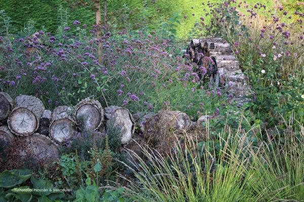 een bostuin of woodland garden met een muurtje van stammetjes